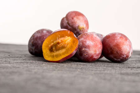 nutritive: Heap of whole fresh plums with one halved one balanced in front showing the juicy texture of the orange flesh and the stone or pip, low angle with copyspace. Stock Photo