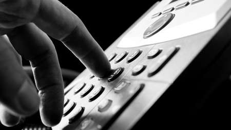 PHONE LINE: Close up of the fingers of a man dialing out on a land line telephone pressing the number keys on the keypad in a communications concept.