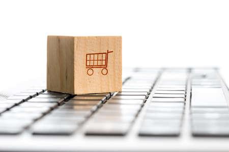 Online winkelen en e-commerce concept met een houten blok met een pictogram van een winkelwagentje staan op een toetsenbord van de computer, bekeken lage hoek met copyspace. Stockfoto