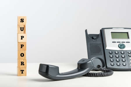Telephone support and communication concept with the word - Support - written on a stack of wooden blocks alongside a landline telephone instrument with the receiver off the hook. photo
