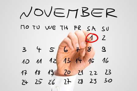 calendario noviembre: Hombre que suena la fecha del 1 de noviembre de Todos los Santos con un marcador rojo como un recordatorio en un calendario escrito a mano que muestra el mes de noviembre.