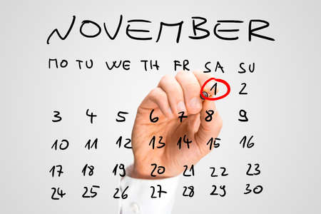 all saints  day: Man ringing the date of 1st November for All Saints Day with a red marker as a reminder on a handwritten calendar showing the month of November.