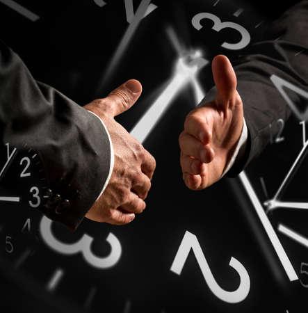 pacto: Tiempo temáticas Imagen de negocios apretón de manos con superposiciones de reloj. Foto de archivo