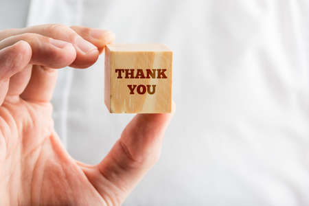 commendation: Close Up of Hand Holding Block with Thank You Written on it. Stock Photo