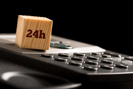 Wooden cube with 24h on a phone keyboard conceptual of twenty four hour business contact and support over a dark background with copyspace. photo