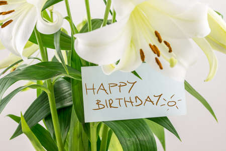 Gift of fresh flowers on a birthday with a bouquet of white lilies with a handwritten note saying Happy birthday, closeup view of the note on green leaves. photo
