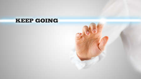 constancy: Motivational Image of Hand Touching Keep Going Statement on Touch Screen.