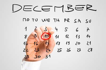 derechos humanos: Hombre que suena Día de los Derechos Humanos, miércoles 10 de diciembre en rojo en un calendario escrito a mano en una interfaz virtual como un recordatorio a sí mismo de su importancia.