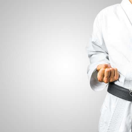 Gedeeltelijke weergave van een man in karate uniform maken van een vuist en het dragen van een zwarte band over grijs met copyspace.