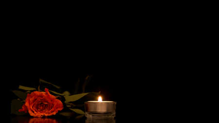 Single romantic orange rose lying on a dark reflective surface with a burning candle against a black background with plenty of copyspace for your Valentines or Anniversary message to a loved one.