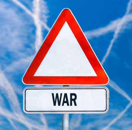 anti war: Triangular traffic warning sign with the word - War - against a blue sky criss-crossed by multiple white contrails from aircraft conceptual of a fight between enemy planes or anti aircraft missiles.