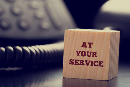 At Your Service written on a wooden cube in front of a telephone conceptual of help, client services, assistance, expertise and consultancy. Foto de archivo