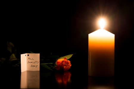 solemnity: Candle burning in the darkness next to a flower during All Saints Day, spiritual symbol of faith and devotion.