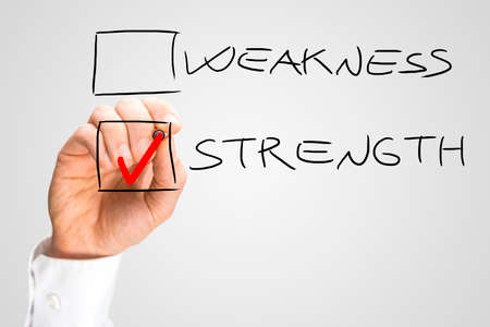 debility: Hand Putting Red Check in Box Next to the Word Strength and Not Next to the Word Weakness. Stock Photo