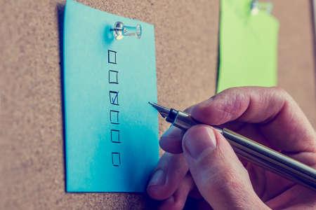 Man tut eine Auswertung auf einem blauen Notiz zu einem Kork Brett Setzen eines Häkchens oder kreuzen sich in einer der Boxen, Nahaufnahme von der Hand und Stift. Standard-Bild