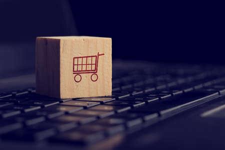 Online winkelen en e-commerce achtergrond met een houten kubus met een winkelwagentje pictogram rust op een toetsenbord van de computer bekeken lage hoek over zwart met copyspace.