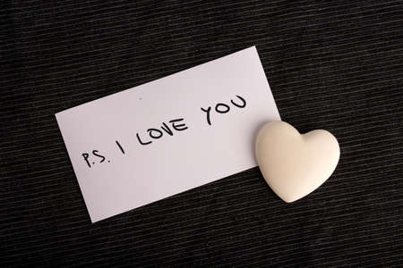 timidity: PS. I Love You handwritten on a white card with a cream colored heart symbolic of love and romance lying on a black background for a Valentines or anniversary greeting or a message to a loved one.