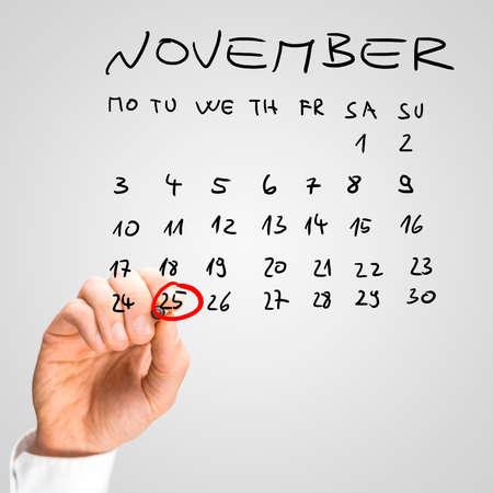 calendario noviembre: Hombre que suena la fecha del 25 de noviembre en rotulador rojo como un recordatorio de que es el Día Internacional para la Eliminación de la Violencia contra la Mujer en un calendario a mano. Foto de archivo