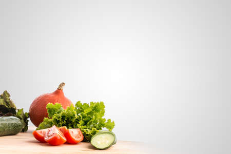 Fresh vegetables and salad ingredients standing ready for cooking on a wooden kitchen table in the bottom left corner of the frame with large copyspace on a grey background.