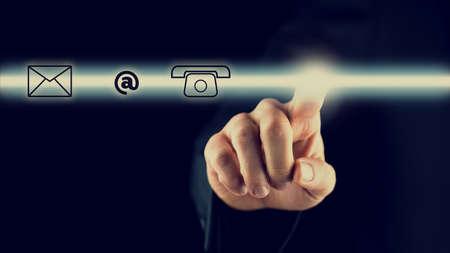 Hombre de activar una barra con iconos de contacto que representan la web, correo, correo electrónico y teléfono en una pantalla virtual o interfaz para soporte y servicio en línea, fondo oscuro con copyspace. Foto de archivo - 32316620