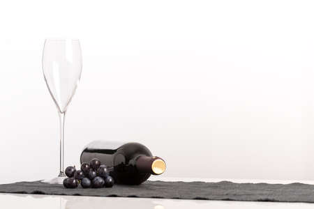 Viticulture and wine concept with an elegant empty wineglass alongside a bunch of black grapes and unlabeled bottle of red wine on its side against a white background with copyspace for your advert. Stock Photo