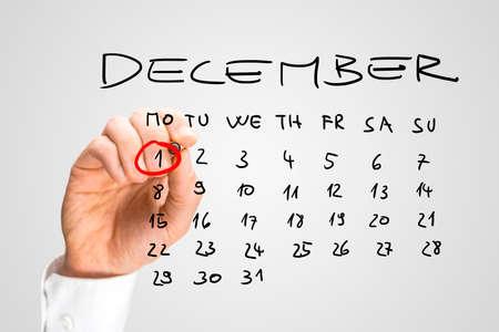 calendario diciembre: Hombre que suena la fecha del 01 de diciembre con un marcador rojo en un calendario a mano como un recordatorio del día Mundial del SIDA.