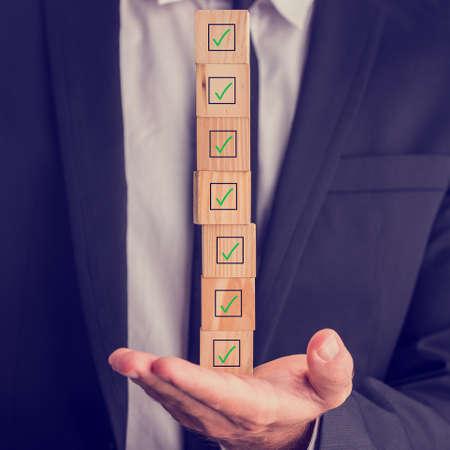 품질, 완료, 승인 또는 투표의 개념 그의 손에 균형 나무 큐브에 표시된 체크 박스의 스택을 들고 사업가입니다.
