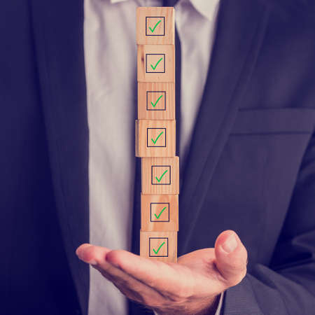 Businessman holding a stack of checked boxes marked on wooden cubes balanced on his hand conceptual of quality, completion, approval or voting. Banque d'images