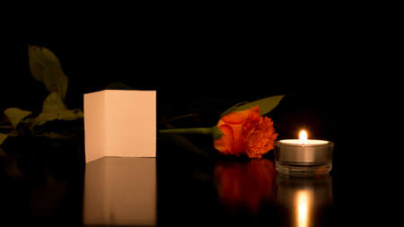 Romantic Still Life of Blank Card with Rose and Candle on Shiny Black Surface. photo