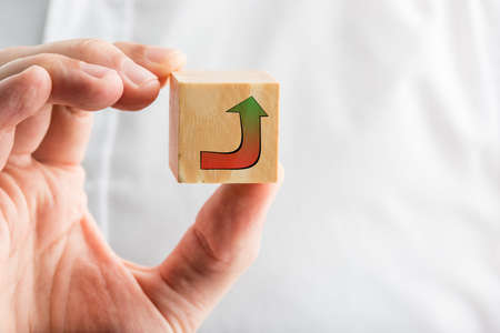 Businessman holding a hand-drawn curving arrow on a wooden block graduating from a red baseline to green at the point showing the route to success. photo