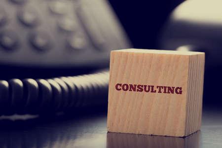 Business Consulting a tema immagine di blocco di legno di fronte a telefono.