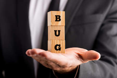 Businessman holding wooden blocks on the palm of his hand with the word Bug. photo