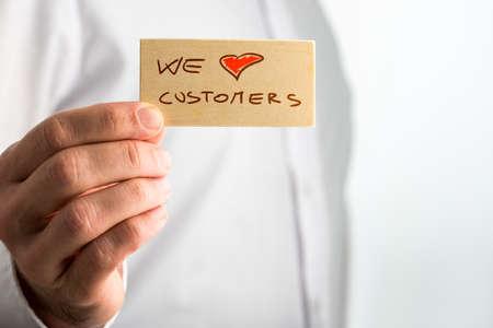 사업가 작은 들고 브라운 우리는 고객 간판을 사랑 해요. 스톡 콘텐츠