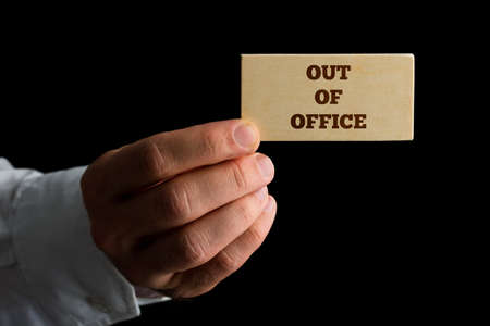 absence: Man holding a business card reading - Out of Office - indicating that he and his services are unavailable due to absence.
