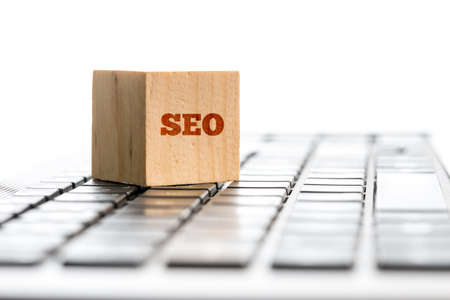 meta: SEO concept with the word written on a wooden block lying on a computer keyboard conceptual of website optimization, copyspace on white behind. Stock Photo