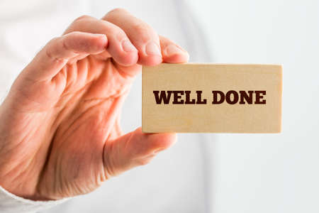 great job: Man Holding Small Piece Wood Showing Well Done Text. Over White Background. Stock Photo