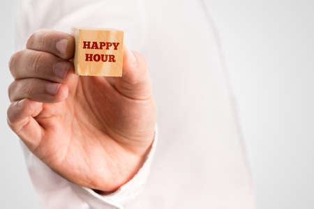 hour hand: Man holding a wooden block reading - Happy hour, close up of his hand with copyspace over his white shirt. Stock Photo