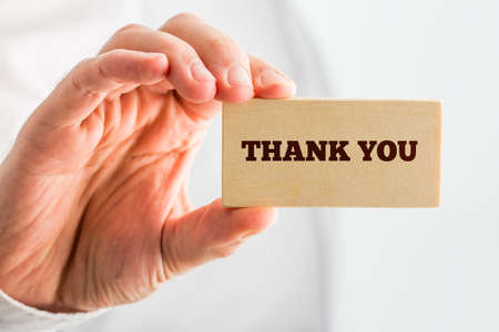 acknowledgment: Close up Thank You Text on Small Piece Wood Hold by Human Hand. Over White Background.