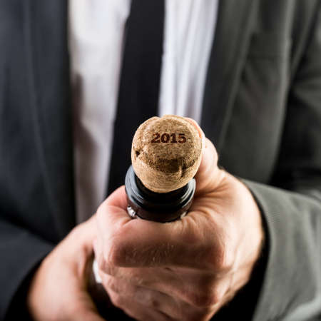 Close up Businessman Opening Bottle of Wine with 2015 Text on the Cork. photo