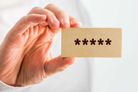 denoting: Man holding a wooden block with five stars denoting top or premium rating or quality, close up of his hand.