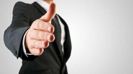 黒のスーツを示すハンドシェイク ジェスチャー近くで実業家を。灰色の背景上に分離。