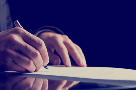 contact us: Close up Human Hand Signing on Formal Paper at the Table on Black Background. Retro Filter Effect. Stock Photo