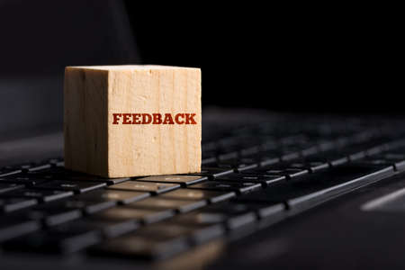 online survey: Close up Feedback Text on Small Wooden Cube on Black Computer Keyboard. Stock Photo