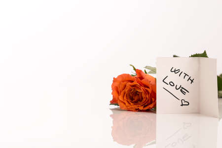 Single orange rose lying on a reflective white surface with a handwritten gift tag saying With Love with copyspace for your Valentines, anniversary, Mothers Day or birthday greeting. photo