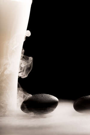 wafting: Wellness concept with smooth basalt spa massage stones with wafting tendrils of smoke against a dark background with zen copyspace.