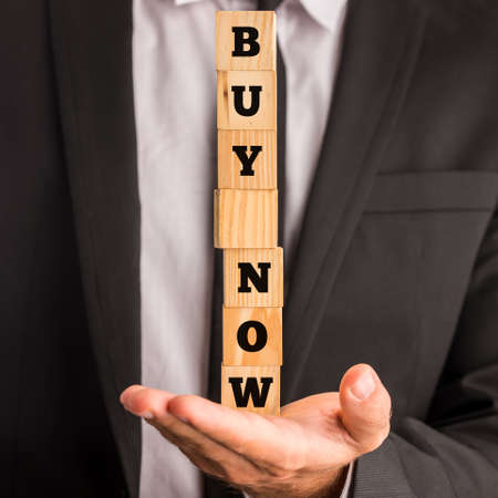 urging: Businessman holding wooden blocks with letters forming a commercial message urging to buy now. Stock Photo