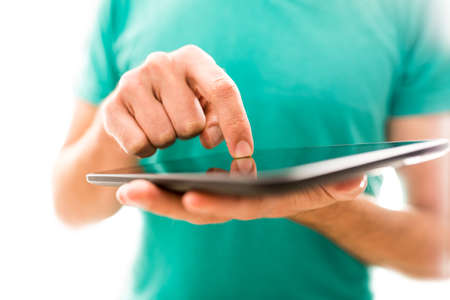 inputting: Young person navigating a tablet computer activating the touchscreen with a finger while surfing the internet or inputting data, close up view of the hands.