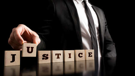 Simple Justice Concept - Close up Businessman in Black Business Suit Arranging Small Wooden Pieces with Justice Text on Black Background. Archivio Fotografico