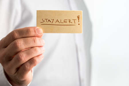 be alert: Close up Simple Stay Alert Concept Design with Businessman Showing Small Wooden Sign with Underlined Stay Alert Texts over White Shirt.