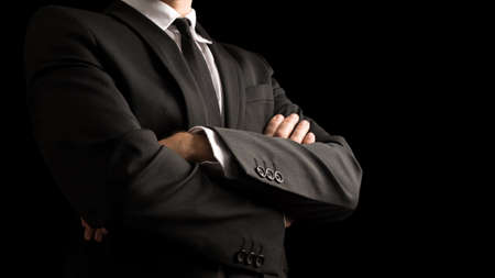 Close up Confident Businessman in Black Elegant Business Suit with Crossed Arms in Front of the Body. Isolated on Black Background. Stock Photo